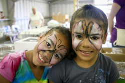 Two smiling girls show off their newly painted faces.